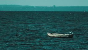 Wooden boat rocking on waves in sea water. Segulls flying over, sunny summer windy day stock footage