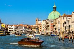 Wooden boat sailing canals of Venice stock photography