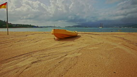 Wooden boat on sand beach against sea islands cloudy blue sky. Camera moves to light brown small wooden boat on yellow sand beach against azure sea distant stock footage