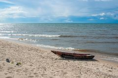 Wooden boat on the sandy shore of lake Baikal, blue sky and calm water. royalty free stock photo