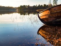 Wooden boat mirrored in water. A wooden boat on the shore mirroring from the still water Stock Images