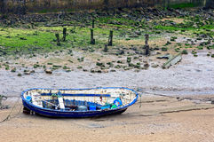 Wooden boat stranded on sand due low tide Royalty Free Stock Photography