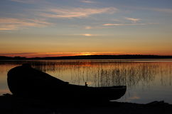 Wooden boat on the sunset lake. Royalty Free Stock Photo