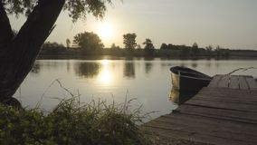 Wooden boat at sunset. Wooden boat near pier on pond at sunset stock footage