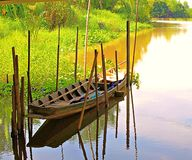 Wooden boat surrounded by bamboo while parked in the canal with neighboring trees. The wooden boat is surrounded by bamboo. Park in the canal with neighboring Stock Image