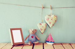 Wooden boat toy and teddy bear over wood table next to blank photo frame and fabric hearts. retro filtered image Royalty Free Stock Photography