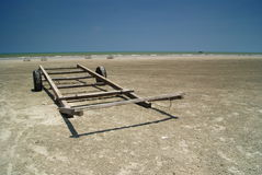 Wooden Boat Trailer on Beach. Wooden trailer for carrying boat to the water lying on the beach Stock Photo