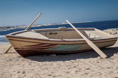 Wooden boat with two oars on beach Royalty Free Stock Image