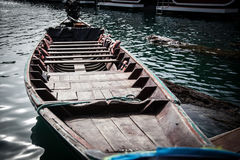 Wooden boat at the wharf . Wooden boat rocking on the water near the pier of a tropical lake royalty free stock image