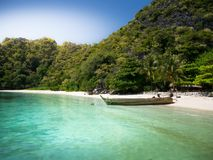 Wooden boat on white sand beach at the sea. Royalty Free Stock Photo