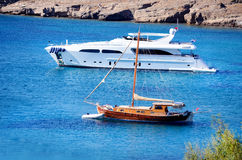 Wooden boat and white yacht in a calm blue sea Royalty Free Stock Images