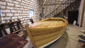 Wooden boat within workshop. Wooden boat with sail mast within workshop. steadicam shoot. Homemade Sailbaot ready to move in sea, lake, or river. Big hobby stock video