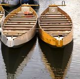 Wooden boats. Two wooden row boats reflected in the water Stock Photo