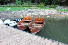 Wooden boats chained to the dock Royalty Free Stock Images