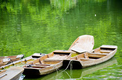 Wooden boats in a lake. Boats in the water on green background Royalty Free Stock Images