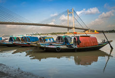 Wooden boats lined up on river Hooghly at Princep Ghat with Vidyasagar bridge (setu) at the backdrop Stock Images