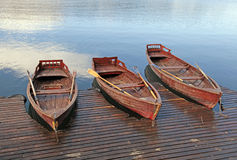 Wooden boats on picture perfect lake Bled, Slovenia. Winter landscape with wooden paddle boats and deck on picture perfect lake Bled, Slovenia. Horizontal image Royalty Free Stock Image