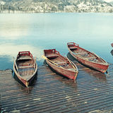 Wooden boats on picture perfect lake Bled, Slovenia. Winter landscape with wooden boats on picture perfect lake Bled, Slovenia. Square toned image, instagram Royalty Free Stock Photography