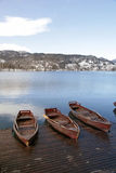 Wooden boats on picture perfect lake Bled, Slovenia. Winter landscape with wooden boats on picture perfect lake Bled, Slovenia. Vertical image Royalty Free Stock Photo