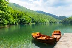 Wooden boats at pier on mountain lake. Biograd lake, Montenegro stock photography