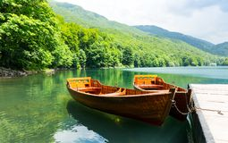 Wooden boats at pier on mountain lake Stock Images