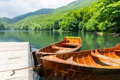 Wooden boats at pier on mountain lake Royalty Free Stock Image