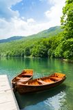 Wooden boats at pier on mountain lake royalty free stock photo
