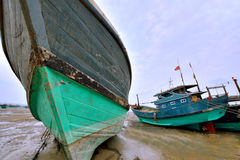 Wooden boats on sand. Wooden fishing boat on beach sand, shown as shipping working equipment and environment Stock Photo