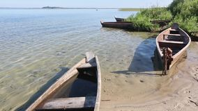 Wooden Boats on Sand near Shore. Wooden boats on sand near shore and summer lake scenery. Figure in boat is unrecognizable stock video footage