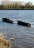 Wooden boats. Two wooden boats breaking moorings on swollen vienne river France Stock Photos