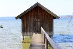 Wooden boatshed on the lake with narrow passage bridge Stock Photos