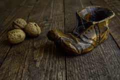 Wooden boots in warm colors on the wooden background Royalty Free Stock Photo