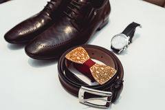 Wooden bow tie, brown leather shoes, belt, watch. Grooms wedding morning. Close up of modern man accessories. Close up of modern man accessories on a white Royalty Free Stock Image