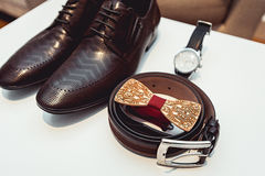 Wooden bow tie, brown leather shoes, belt, watch. Grooms wedding morning. Close up of modern man accessories. Close up of modern man accessories on a white Royalty Free Stock Images