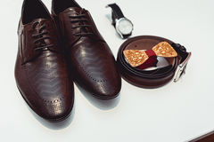 Wooden bow tie, brown leather shoes, belt, watch. Grooms wedding morning. Close up of modern man accessories. Close up of modern man accessories on a white Stock Images