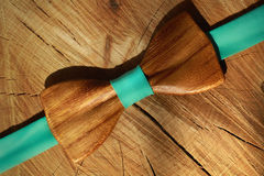 Wooden bow tie with ribbon mint colour lay on dry wood background. Diagonal line, flat lay. Natural and eco fashion Royalty Free Stock Photography