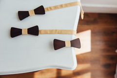 Wooden bow ties on a ivory table Stock Images