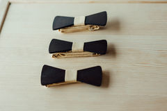 Wooden bow ties on a ivory table Royalty Free Stock Photos