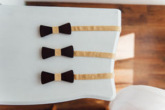 Wooden bow ties on a ivory table Royalty Free Stock Photography