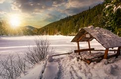 Wooden bower in snowy winter forest at sunset Royalty Free Stock Photo