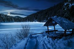Wooden bower in snowy winter forest at night. Wooden bower in snowy winter spruce forest. beautiful mountainous landscape near snow covered frozen lake at night stock photo
