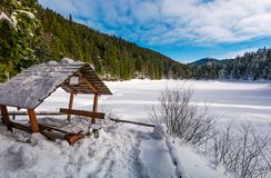 Wooden bower in snowy winter spruce forest. Beautiful mountainous landscape near snow covered frozen lake Synevyr Stock Photography