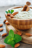 Wooden bowl with almond flour and green mint close up. Stock Image