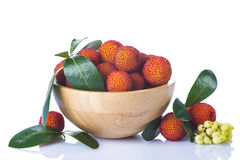 Wooden bowl with arbutus unedo fruits. Isolated on a white background Stock Photography