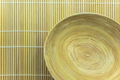 Wooden bowl on bamboo mat Royalty Free Stock Photo