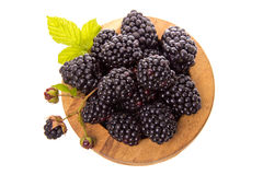 Wooden bowl with blackberry. Blackberries in a wooden bowl on a white background Stock Image