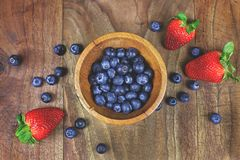 Wooden Bowl of Blueberries with Fresh Strawberries on Rustic Wood Plank Background stock photos