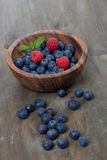 Wooden bowl with blueberries and raspberries, vertical. Close-up Stock Photos