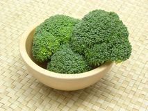 Wooden bowl with broccoli. On rattan underlay Stock Photo