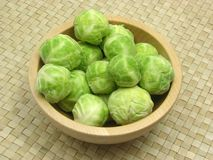 Wooden bowl with brussels sprouts. On rattan underlay Stock Image